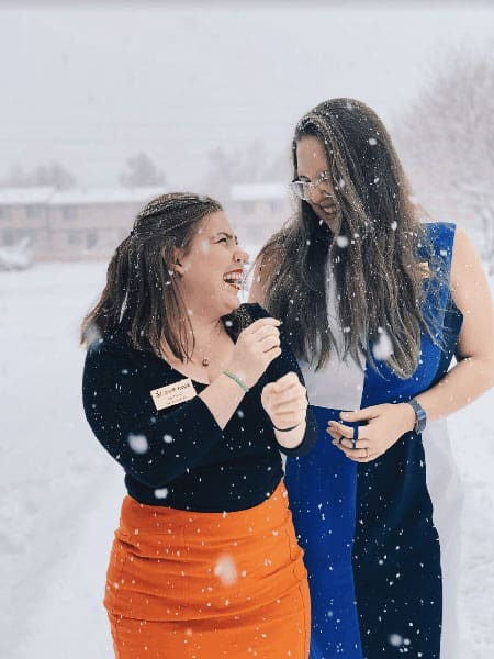 Two study abroad students playin gin the snow in winter