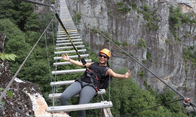 Young adult female walking on adventure challenge bridge over a canyon