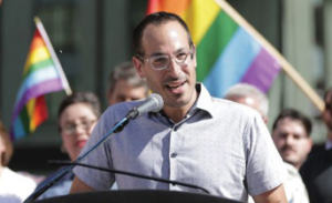 Ryan Lympus featured speaking at a podium at an event with LGBT Pride flags in the background